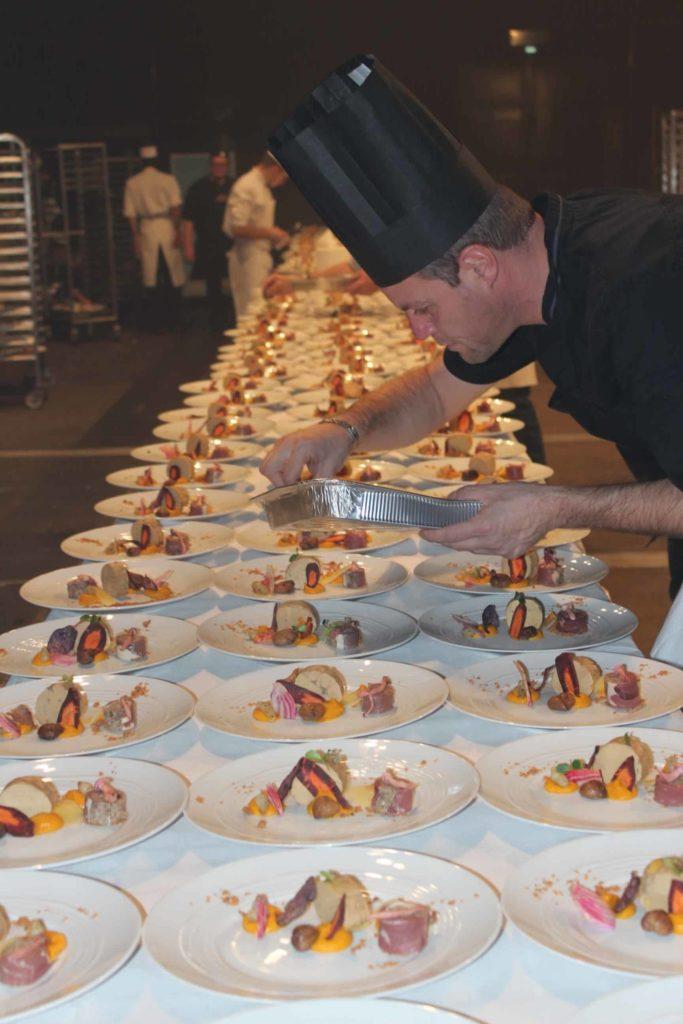 Photo du chef de cuisine entrain de dresser les assiettes d'entrées au foie gras pour 1200 personnes Montrognon Traiteur